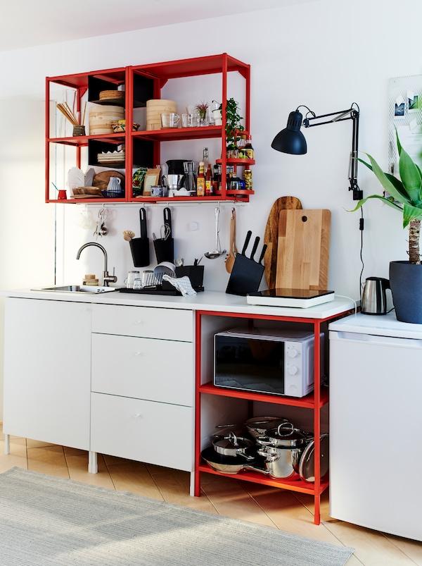 一个设备齐全的小厨房,包括ENHET 安纳特 储物组合:红色开放式储物装置和白色封闭式储物装置。