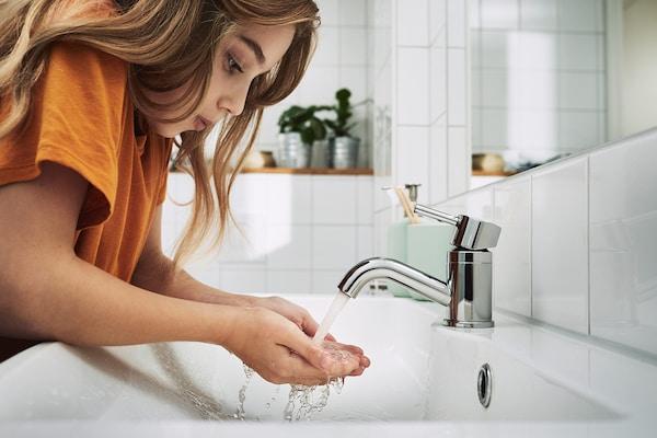 一个身穿T恤的小女孩用双手接住从浴室水龙头里流出来的水。