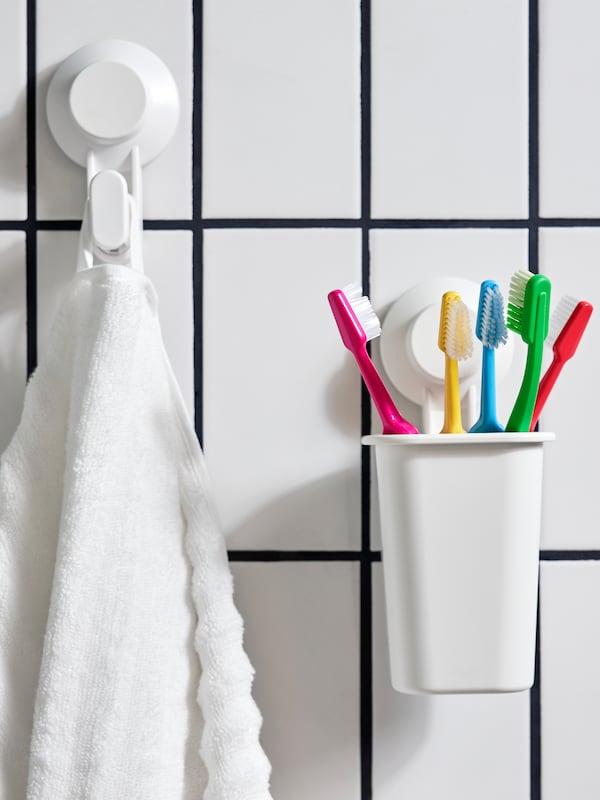 一个TISKEN 提斯科恩 牙刷架,其中放着五根不同颜色的牙刷;旁边有一个带吸盘挂钩,挂着一条白色毛巾。