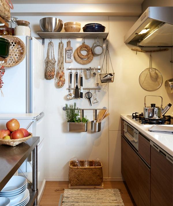 一个狭窄的厨房里,设有深色储物柜,厨具挂在金属挂杆上,端墙处装有搁板。