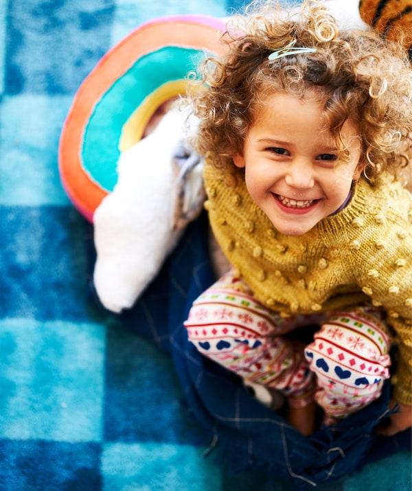 一个小孩面带微笑,坐在蓝色格纹地毯上的深蓝色休闲毯上。