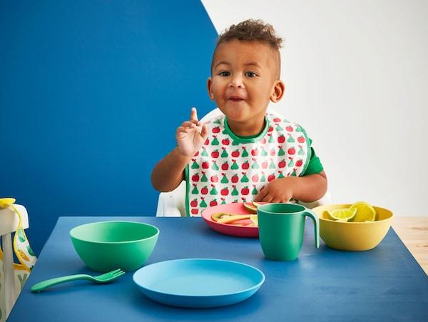 一个小孩在桌边吃饭,面前摆着由PLA塑料制成的蓝、绿、黄和红色的宜家 HEROISK 希罗斯 餐具系列。
