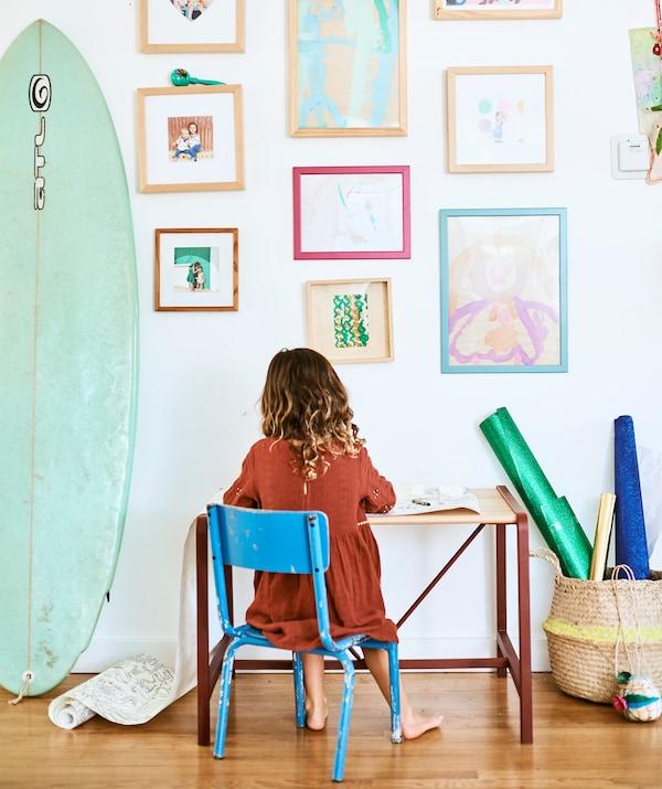 一个小孩坐在小桌子前的蓝色椅子上,背靠墙壁,墙上挂着孩子们的画作和家庭照片,旁边放有冲浪板。
