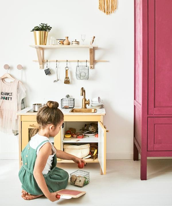 一个小女孩在玩独立橱柜,配有玩具煎锅、食物和挂在搁板上的厨房用具。