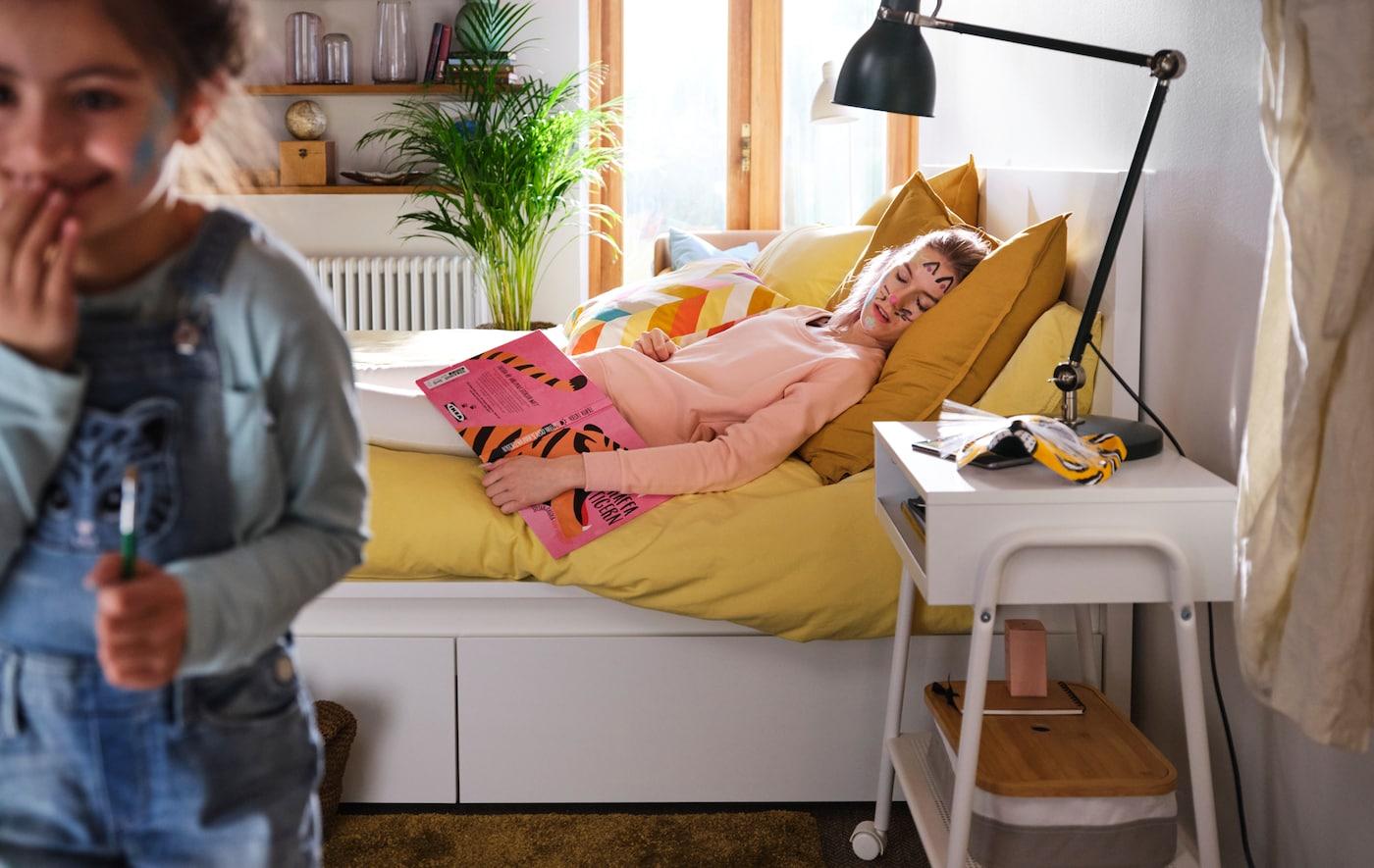 一个小女孩正偷偷从一间风格现代的卧室中溜出,她的妈妈躺在一张 MALM 马尔姆床上,脸上是小女孩刚刚画上的猫胡子。