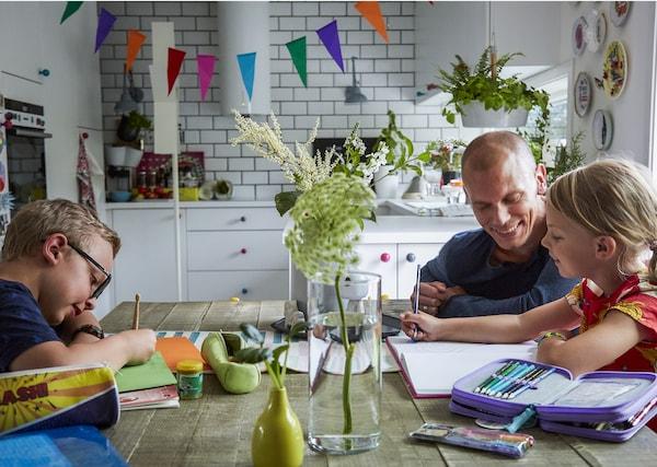 一家人在桌子周围温习功课。