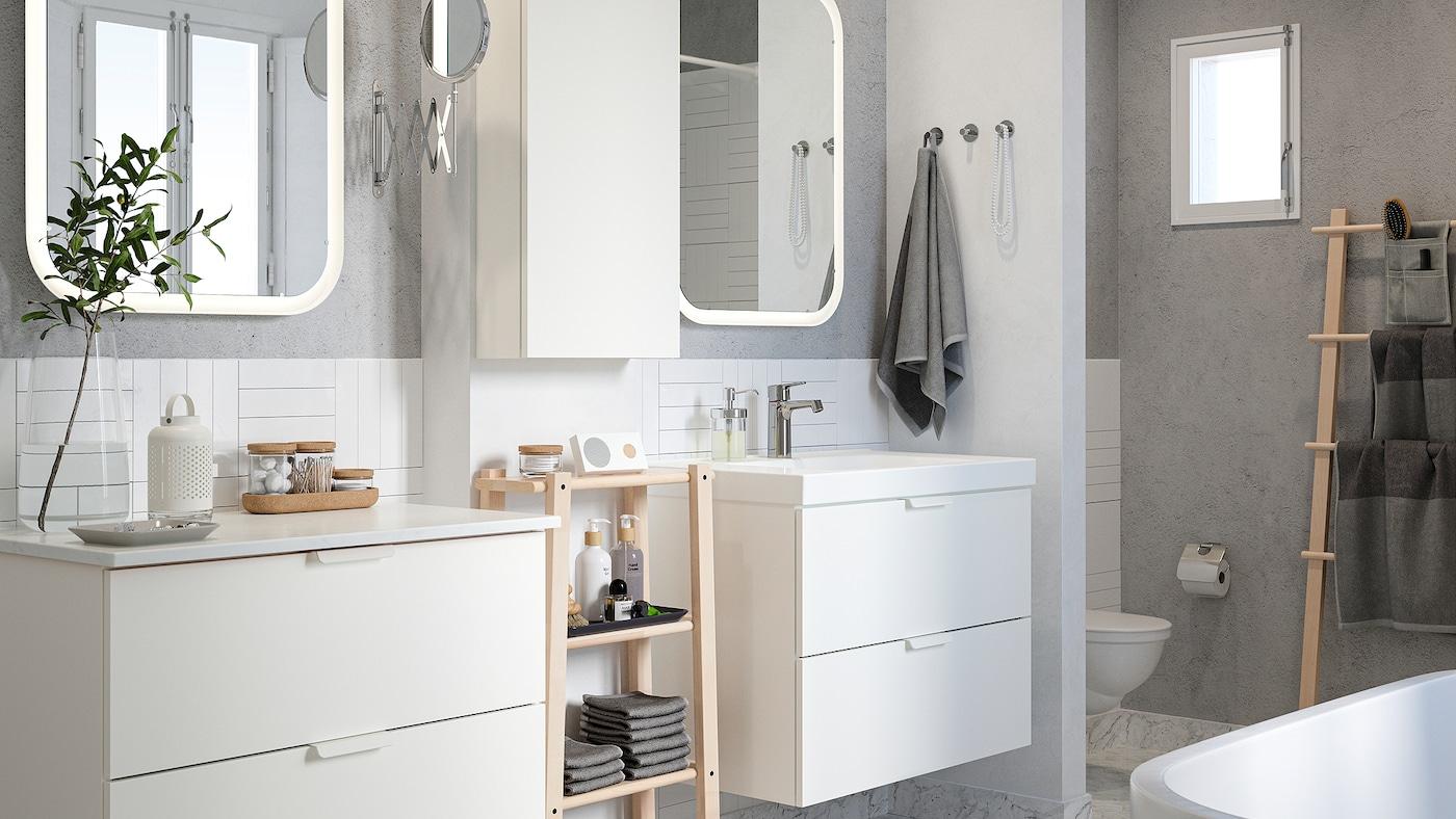 一间白色瓷砖浴室,配灰色墙面,两个脸池架、镜子和桦木搁架,上面放着毛巾和化妆品。