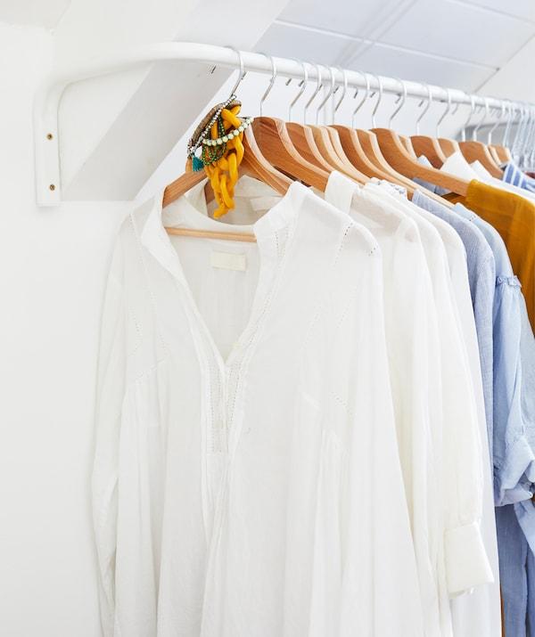 一间白色的卧室里,白色的挂杆上挂着一些木质衣架,衣架上挂着衣服。