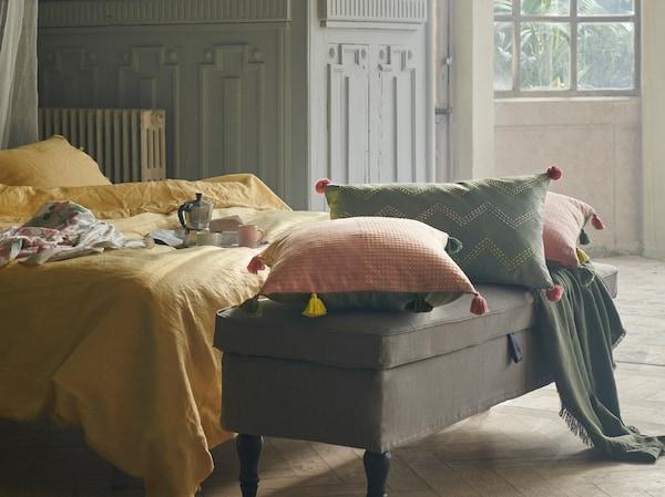 一间充满梦幻气息的卧室,床尾长凳上摆有粉色和绿色的 KLARAFINA 可拉菲娜 和 MOAKAJSA 沐奥柯 垫套。