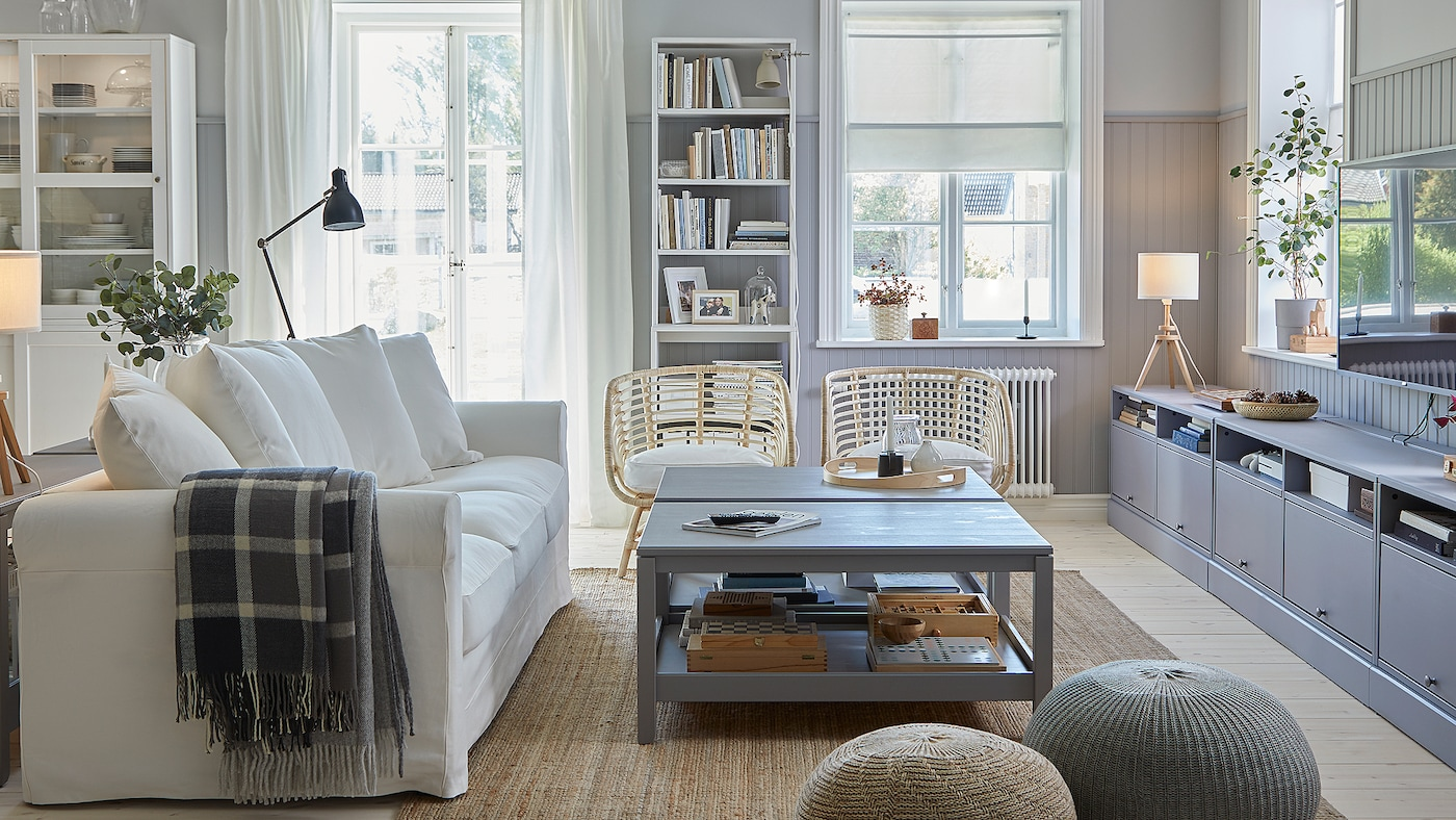 一间传统的客厅里放着白色沙发、铺着黄麻地毯,还有两张灰色茶几、一张灰色电视柜和两把藤编扶手椅。
