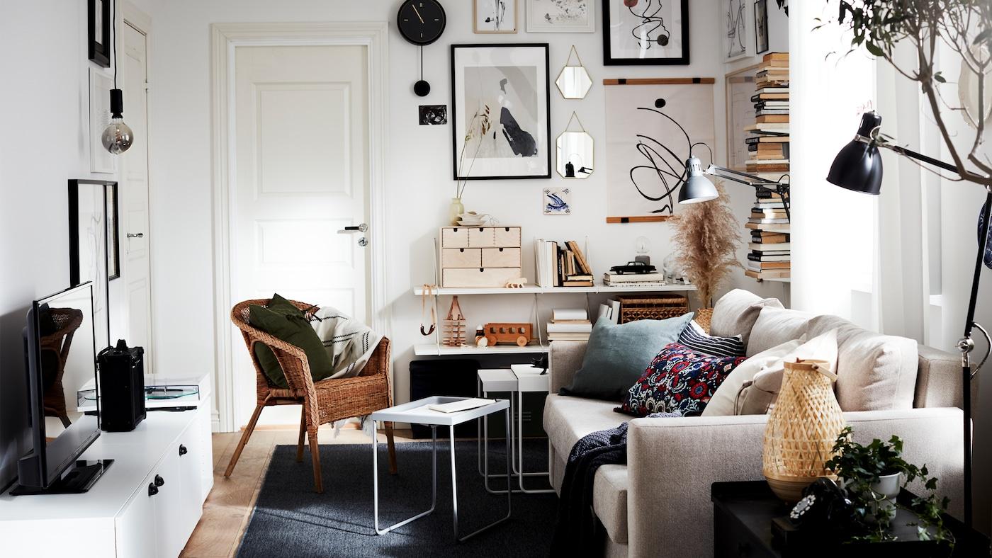 一间光线充足的小客厅,配有沙发、电视机、立式书架和挂满艺术品的墙壁,均为中性色调。
