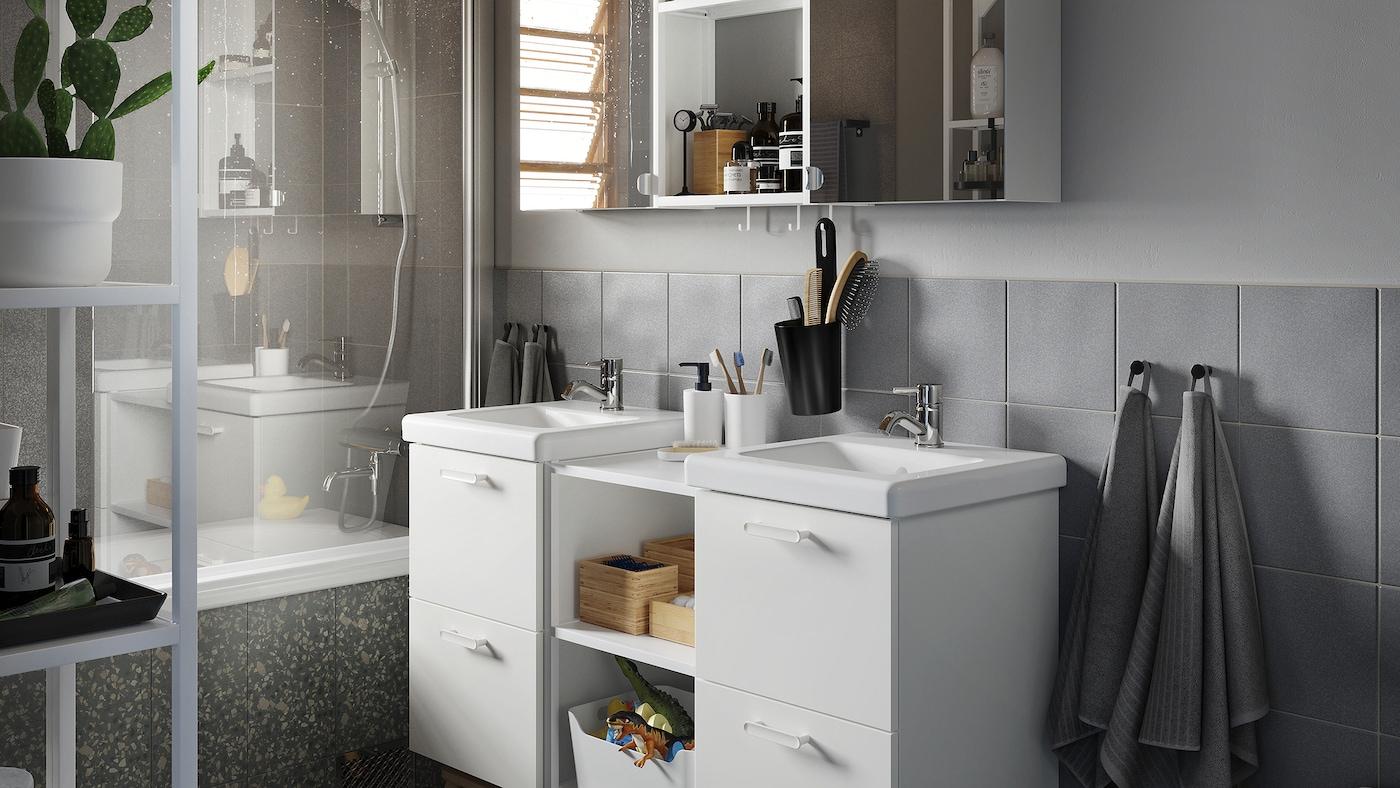 一间灰色基调的浴室,内有白色脸池架和洗脸池、一个镜门柜和一些竹艺配件。