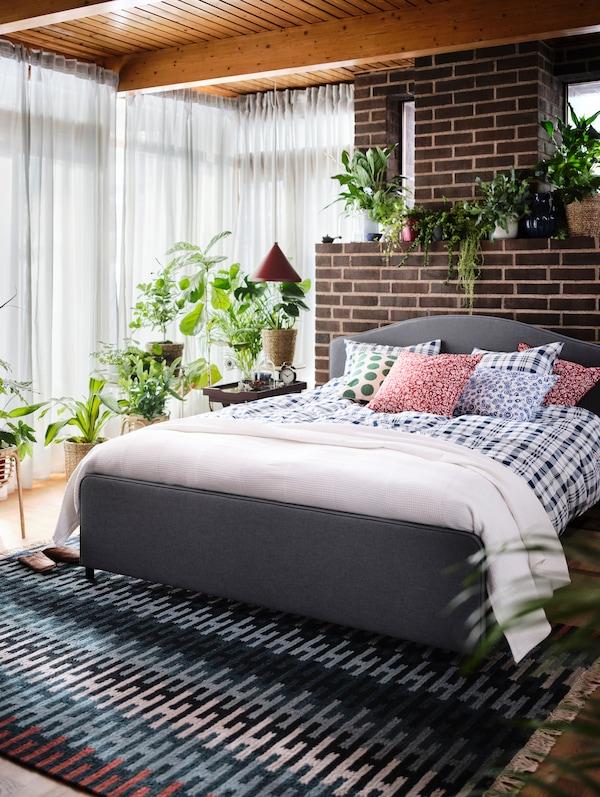 一间明亮的卧室中,布置着一张HAUGA 豪嘉 软包床、多彩的RESENSTAD 瑞塞斯塔 地毯和随处可见的绿色植物。