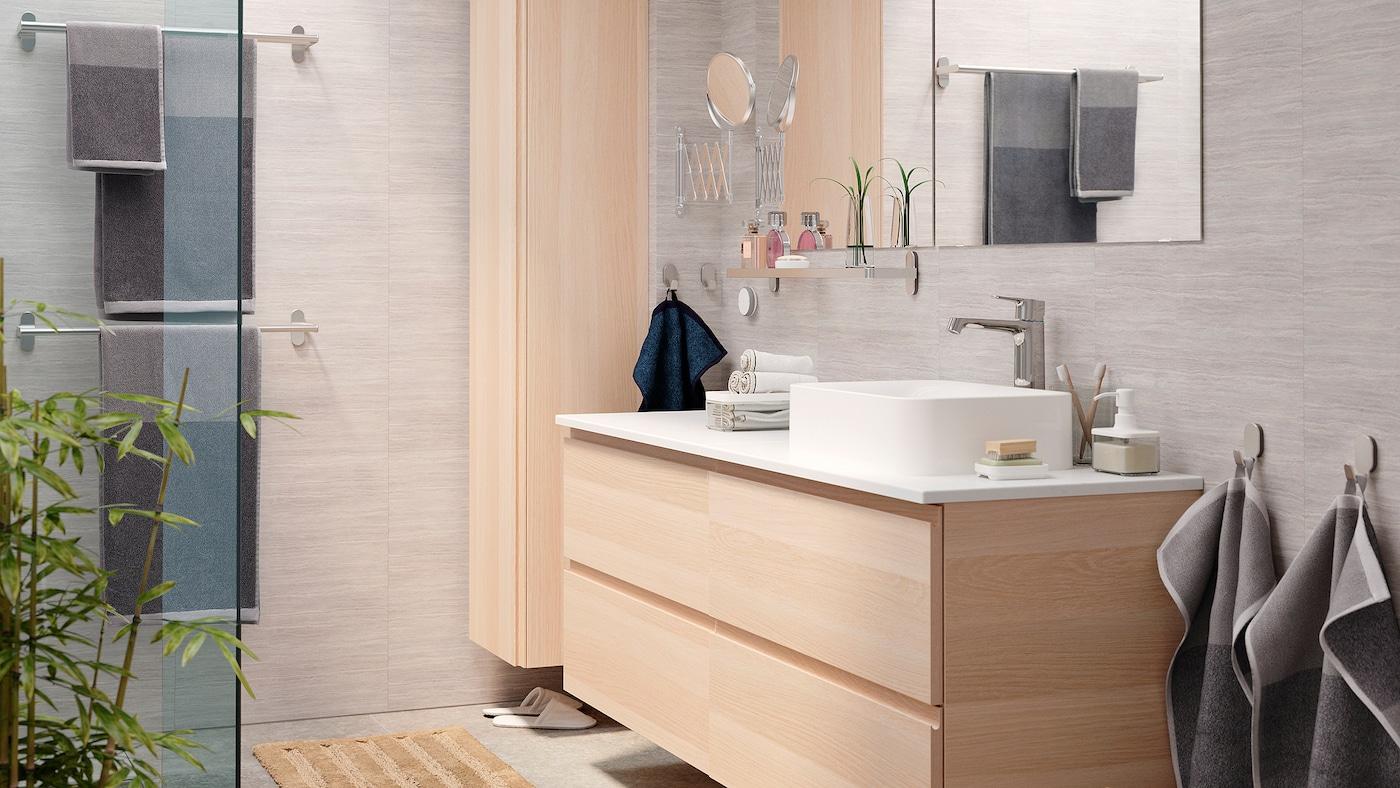 一间明亮优雅的浴室,其中有一个白色仿橡木纹GODMORGON 古德莫 脸池架和一个GODMORGON 古德莫 高柜。