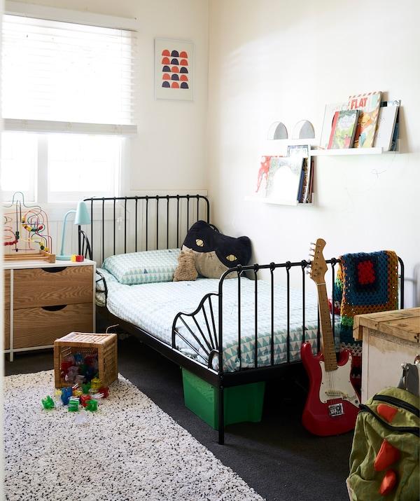 一间配有白色墙壁和黑色床架的儿童房,里面的壁式图片架上还放着几本书。