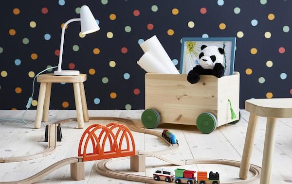 一间铺有波尔卡圆点墙纸的房间里摆放着木制玩具火车套件、带轮的木质玩具储物箱和小木凳。