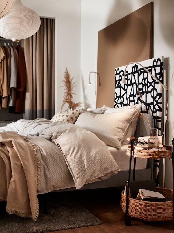 一间卧室,里面有一张灰色的SLATTUM 斯拉图 软垫床架、米色的BERGPALM 贝利帕姆 被套和枕套。