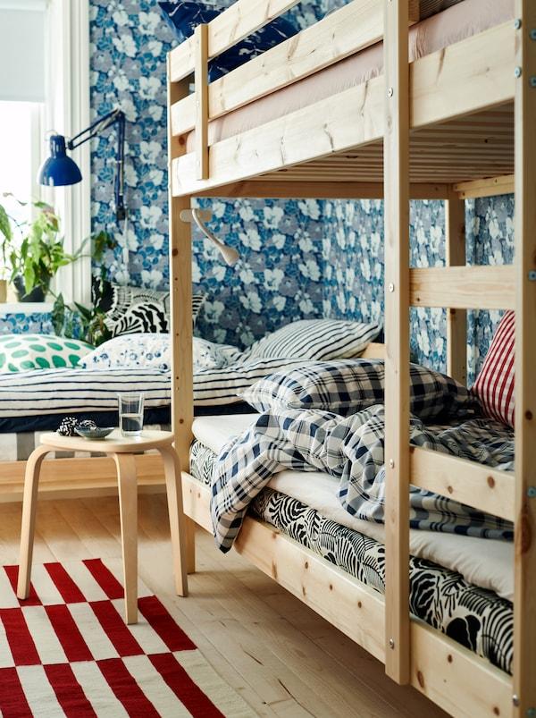 一间卧室,配有一张中性色调的床和一张双层床、花卉图案墙纸以及不同颜色和图案的纺织品。