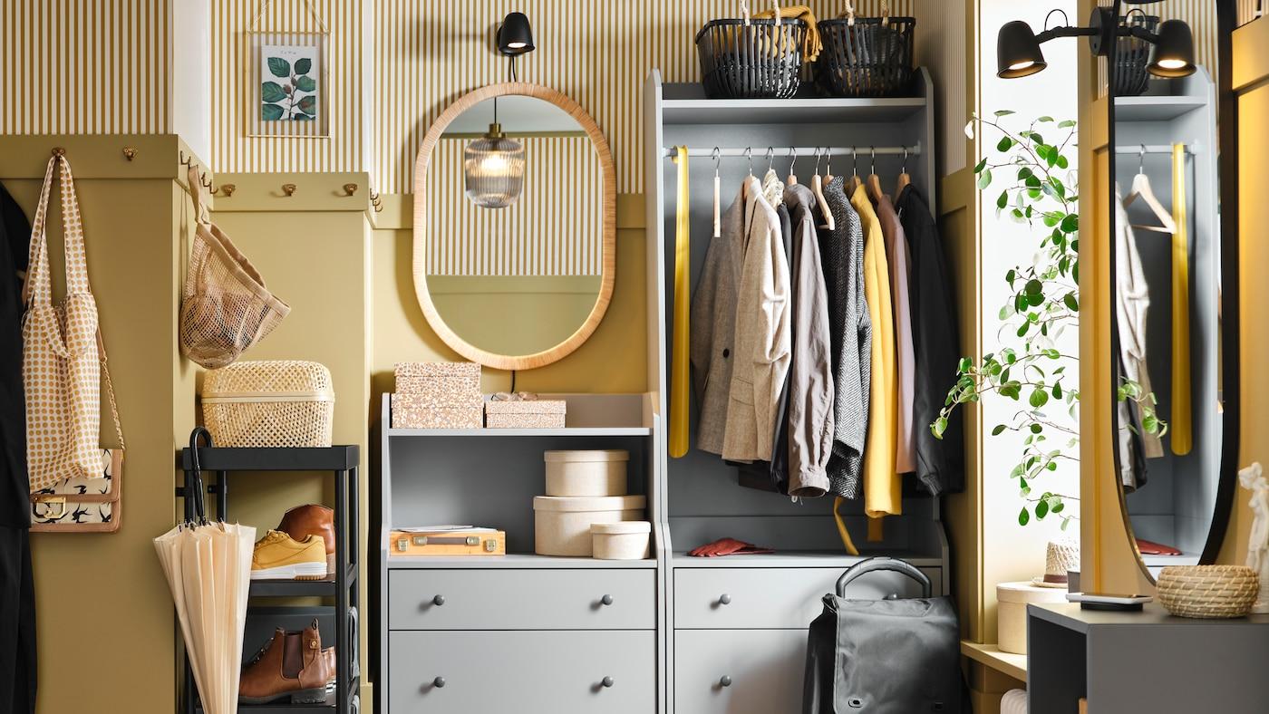 一间狭小的门厅里,有一个HAUGA 豪嘉 抽屉柜和一个HAUGA 豪嘉 开放式衣柜,上面放着衣服、储物盒和篮子。