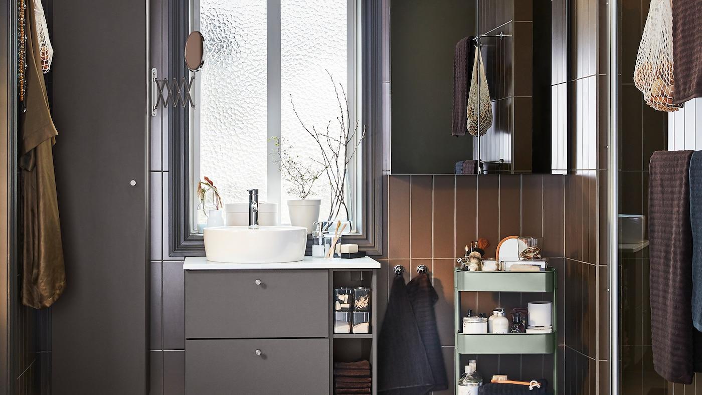 一间浴室内陈设有深灰色浴室家具,还有一个镜门柜和一个灰绿色手推车。