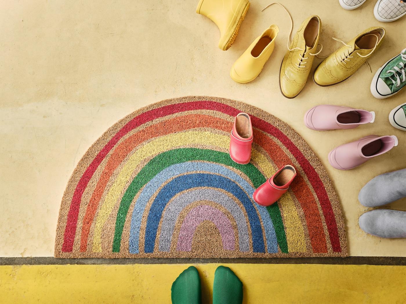 一块带有彩虹图案的PILLEMARK 皮利玛克 门垫铺在黄色的地板上,上面摆放着各种颜色的鞋子,还有一双穿着绿袜子的脚。