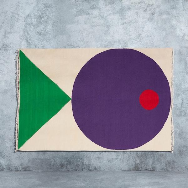 """一块米色手织地毯,上面的几何图案呈现出一条彩色的快乐小鱼。该地毯由Seulgi Lee专为""""宜家艺术节2019""""设计。"""