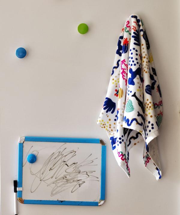 一块配有笔的小白板,一块带图案的布料挂在彩色的挂钩上。