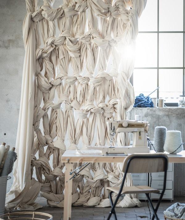 一块由绳结布料制成的窗帘挂在一张桌子后,桌子上摆放着一台缝纫机。