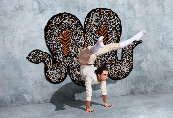 """一块棕色、白色和橙色蛇形图案地毯,上面织有花卉图案。该地毯由Supakitch专为""""宜家艺术节2019""""设计。"""
