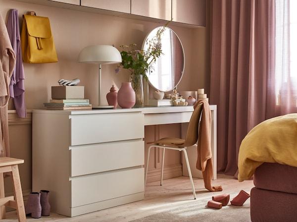 一款白色抽屉柜,一款白色梳妆台,一盏白色台灯,粉色小花瓶和白色圆镜子。
