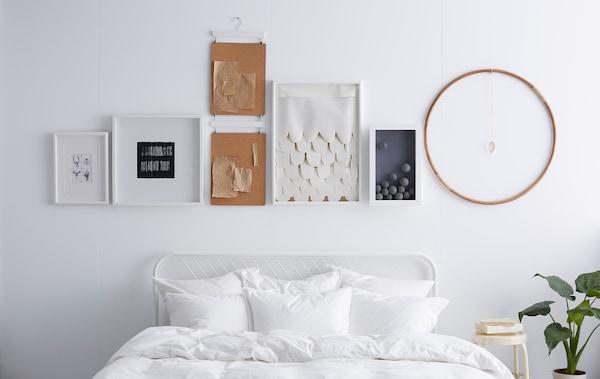 一面白墙,上面悬挂着画框和排成直线的物品。