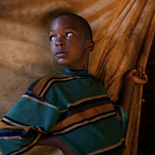 一名非洲男孩站在难民营的住所外。