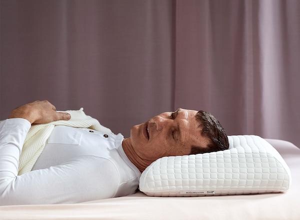 一名男士仰卧着枕在宜家 MJÖLKKLOCKA 缪克洛卡 人体工学枕上,睡得很沉。
