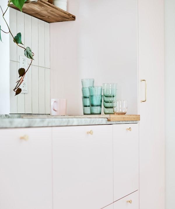 一排粉色柜门橱柜单元,一摞绿色玻璃杯和粉色马克杯放在大理石操作台面上的砧板上。