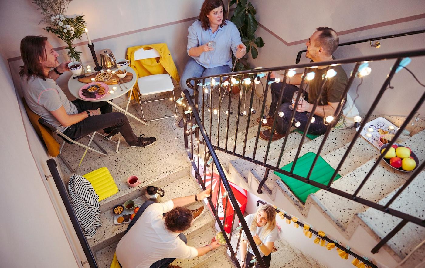 一群男女高低错落地坐在楼梯间里,正一边聊天,一边共享零食。
