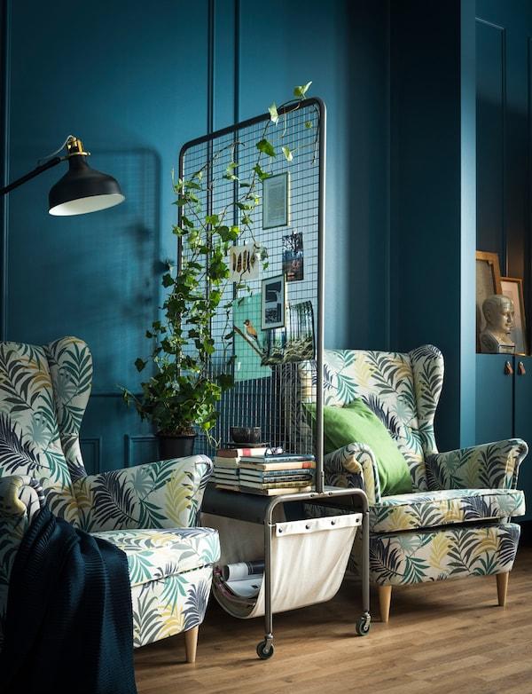 一扇房间隔板隔开了两把扶手椅,隔板上摆放着植物、杂志和书。