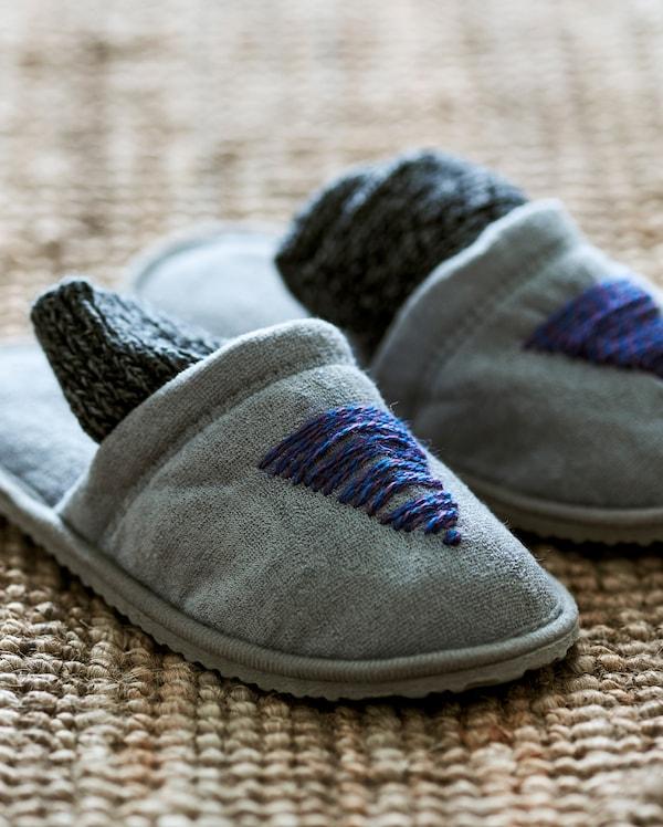 一双灰色拖鞋放在黄麻毯上,拖鞋前部饰有蓝色羊毛线缝制的定制冷杉图案。