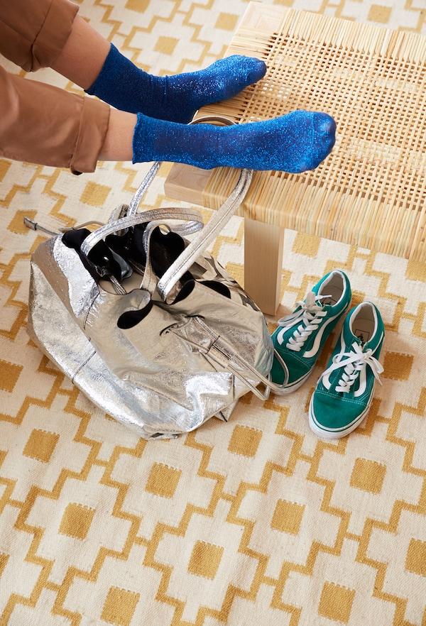 一双脚放在一张藤条茶几上,旁边是一个银色背包和绿色鞋子,地毯带有黄色图案。
