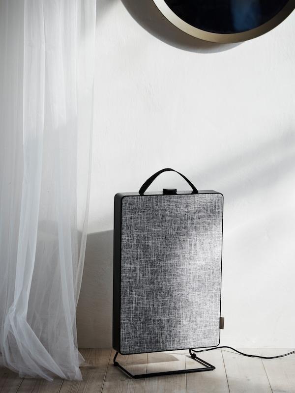 一台黑色的 FÖRNUFTIG 费努福提 空气净化器,配灰色布料正面和黑色提手,插着电线,旁边是白色的透光窗帘。