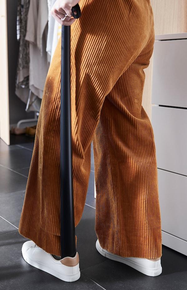 一位穿着灯芯绒裤的女士站着用 OMTÄNKSAM 沃姆安克萨姆 鞋拔子穿鞋。