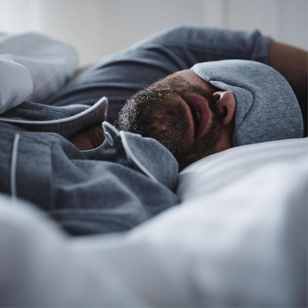 一位穿着蓝色睡衣的男士戴着配套的眼罩,嘴巴微张睡在床上。