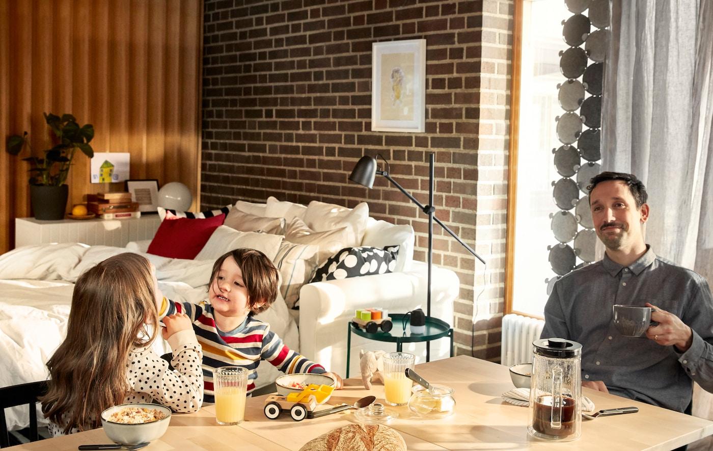 一位父亲坐在早餐桌旁悠然地喝着咖啡,他的两个孩子在身边捣弄着自己的食物。