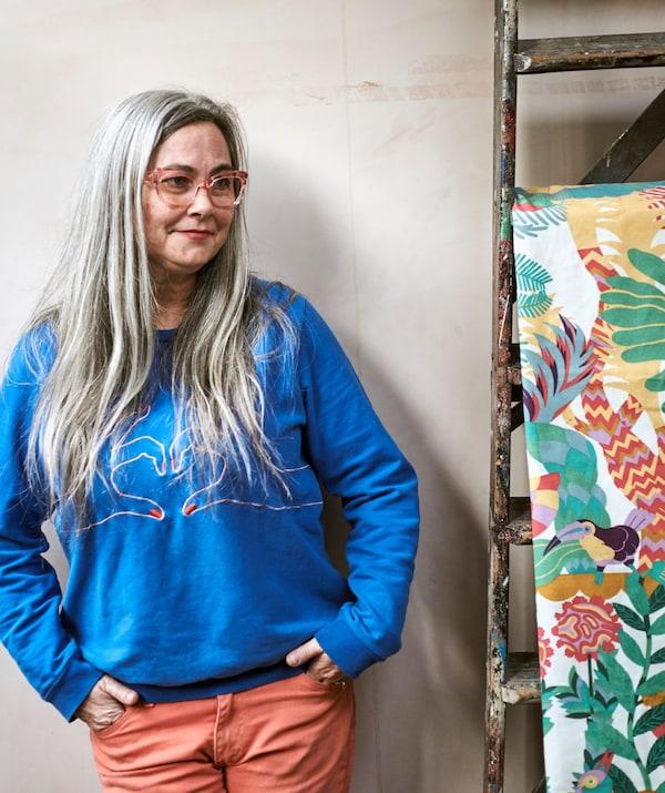 一位留着灰白长发,戴着粉红色框架眼镜,穿着蓝色运动衫的女士,旁边是悬挂在梯子上明艳动人且饰有图案的布料。