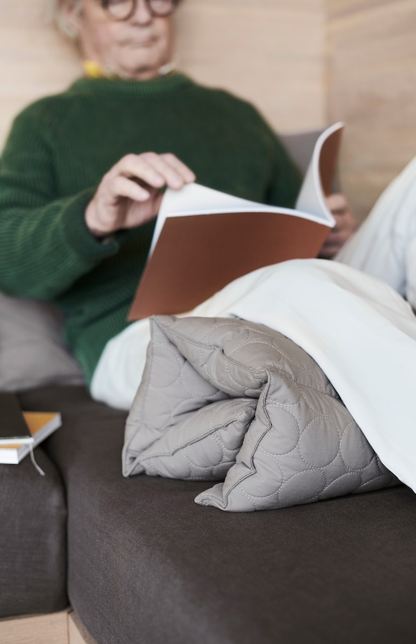 一位六十几岁的男士靠在墙上看书。膝盖下垫着 OMTÄNKSAM 沃姆安克萨姆 连排多靠垫。