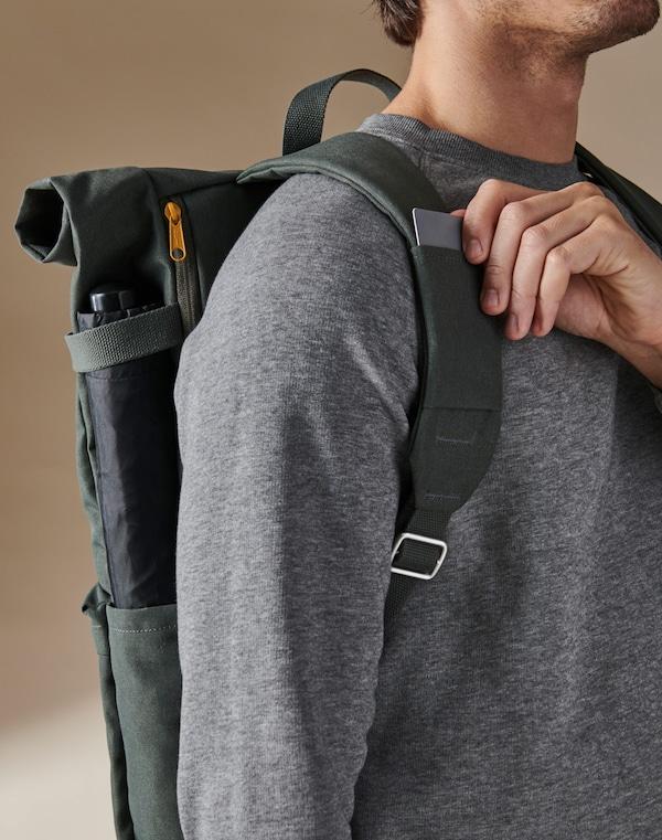 一位男士背着绿色 DRÖMSÄCK 德姆塞克 背包,从肩带上的卡槽里取出一张卡。