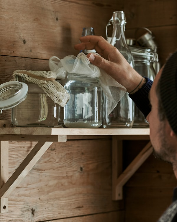 一位男士从木材搁板上拿起一个附棉布内衬盖子的Kilner式玻璃罐。
