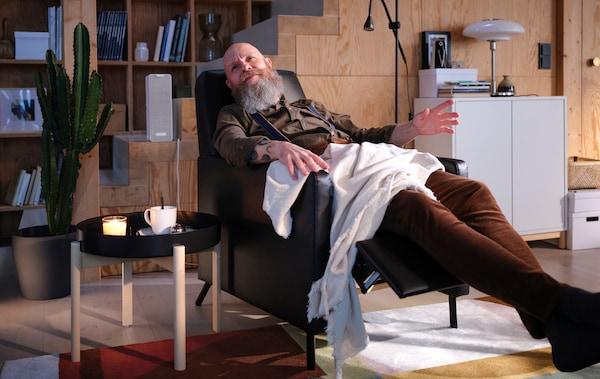 一位男士盖着毯子躺在一张黑色的GISTAD 基斯塔 躺椅中,听着白色SYMFONISK 希姆弗斯 WiFi音箱中播放的音乐。