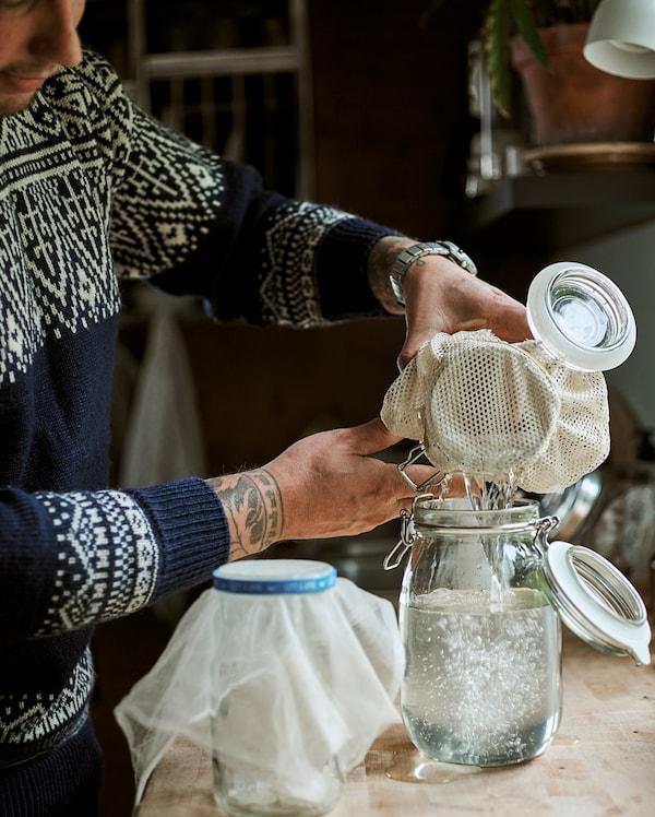 一位男士在厨房用凳上,将Kilner式玻璃罐中的干净液体倒进另一个将棉布用作滤水器的罐子中。