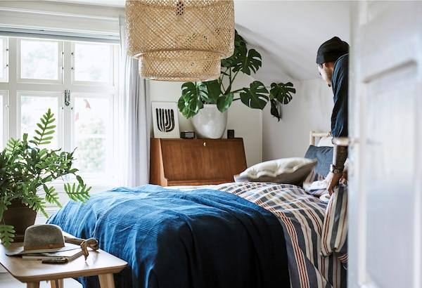 一位男士在制作床具,房间内有红、白、蓝条纹被和深蓝色休闲毯,以及大型编织吸顶灯。