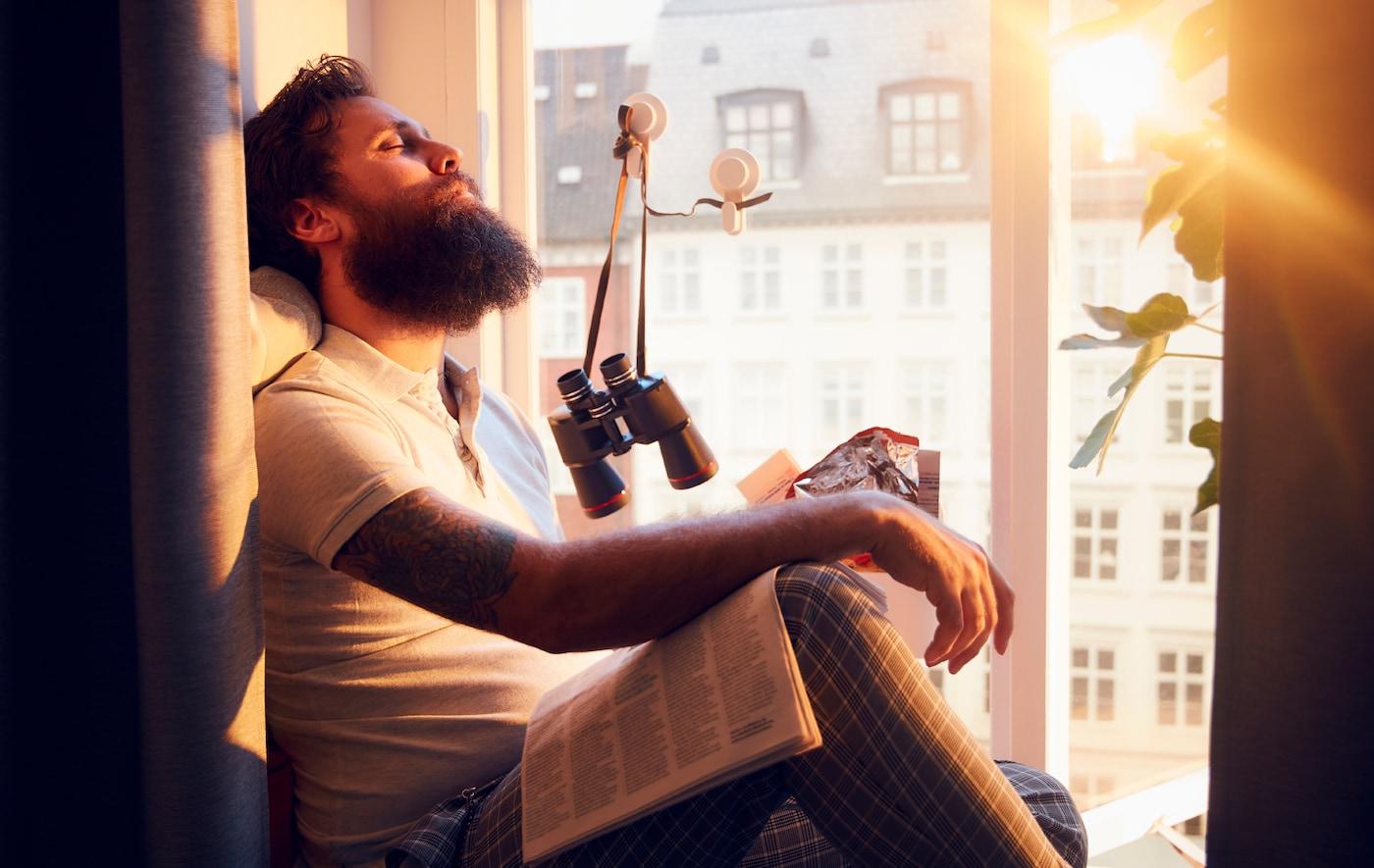 一位男士坐在洒满阳光的深长窗台上,头向后靠着。背景为多层建筑的正立面。